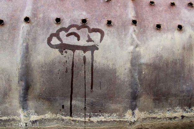 Raincloud painted with water on a rusted drum. drying quickly.