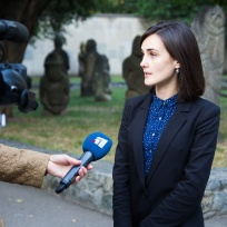 Ms Iryna Polikarchuk, Director Artsvit Gallery, giving a TV Interview with the Baba Figures in the background